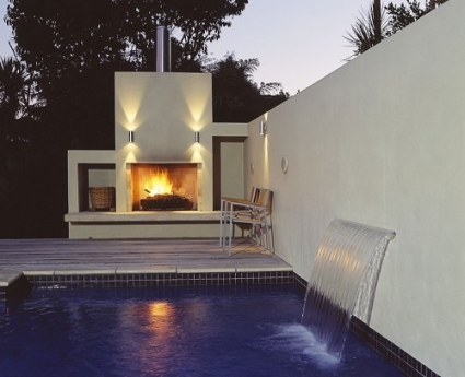 Water fountain into pool from plastered block wall